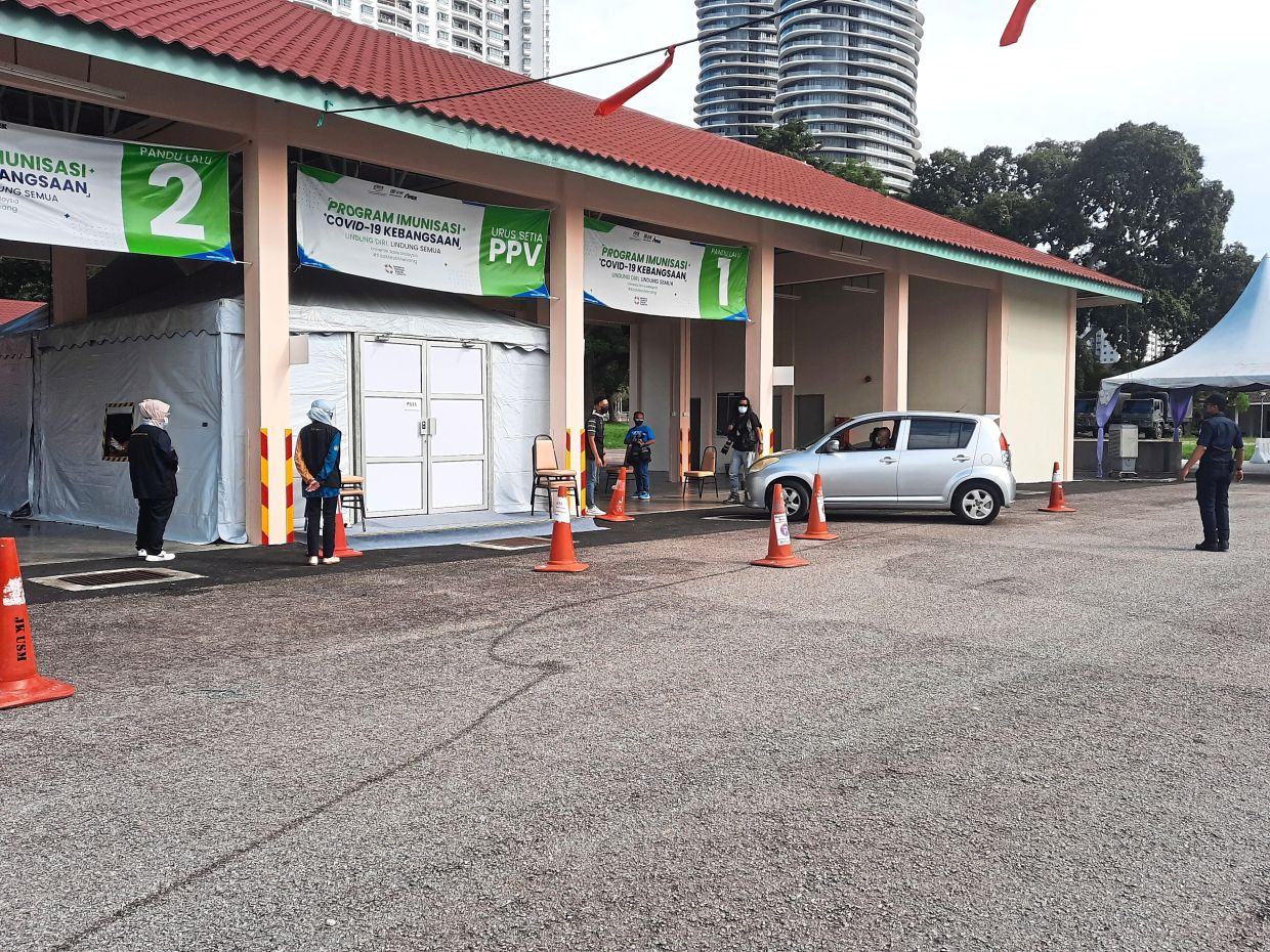Vaccine recipients coming in for their jabs at the drive-thru vaccination centre at USM's main campus in Gelugor, Penang. — RENA LIM/The Star
