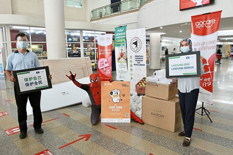 Lifting spirits: Ngang in his Spider-Man costume presenting donations of stationery and food packets to Hospital Ampang. With him are Amira Nashuha and Selangor CRSM chief Ch'ng Soo Chau.