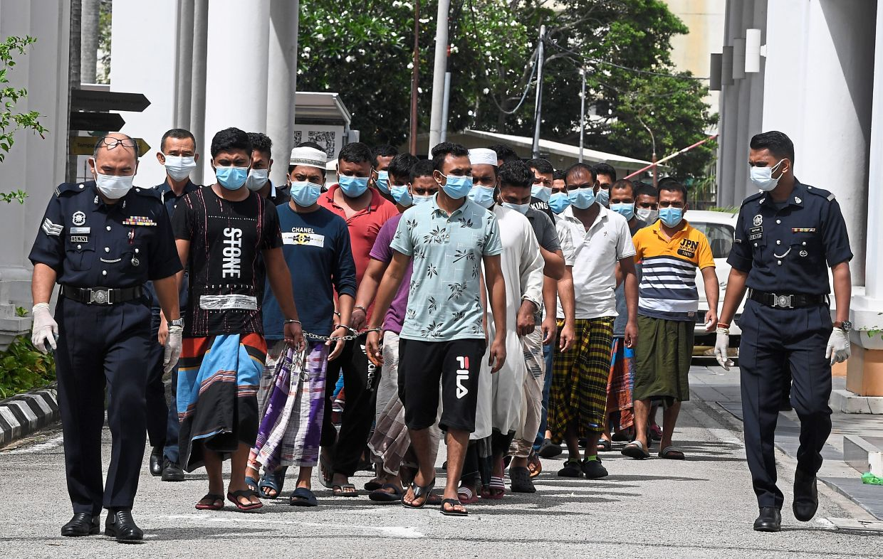 Facing the music: Police escorting the 25 after they were fined by a court in George Town. — Bernama