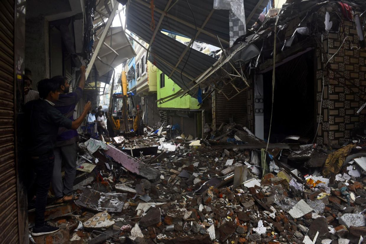 People use their phones to take pictures of a collapsed building following rains in Mumbai, on July 23, 2021. - Reuters