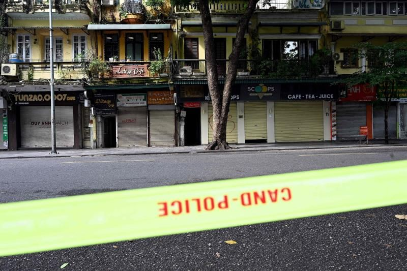 Closed shops and eateries are seen past police tape past along a deserted street in Hanoi on Saturday, July 24, 2021, the first day of a government imposed two-week lockdown to stop the spread of the Covid-19 coronavirus. - AFP