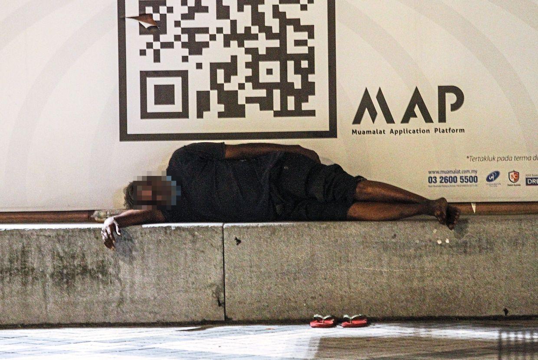 A man sleeping soundly in Lebuh Pasar Besar, Kuala Lumpur.