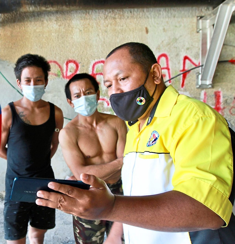 Rashdan (right) talking to some homeless people living under a bridge in Kuala Lumpur.