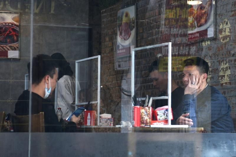 People sit in a restaurant behind plastic dividers as a measure against the sread of the coronavirus disease (Covid-19) in Hanoi, Vietnam. - Reuters