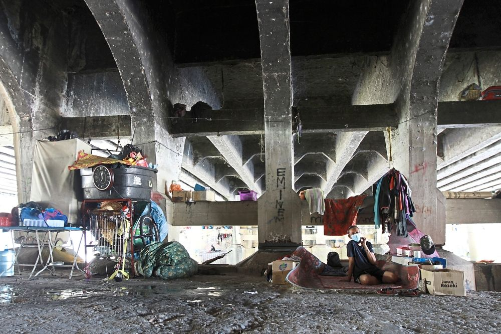 Shelter from the elements: Surrounded by his possessions, a man takes refuge under this bridge near a riverbank in Kuala Lumpur. — LOW LAY PHON/The Star