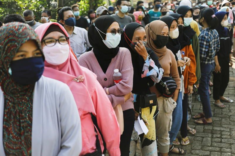 People wearing protective face masks queue to receive a dose of China's Sinovac Biotech vaccine for coronavirus disease (Covid-19) during a mass vaccination program at a school building in Jakarta, Indonesia, July 26, 2021. - Reuters