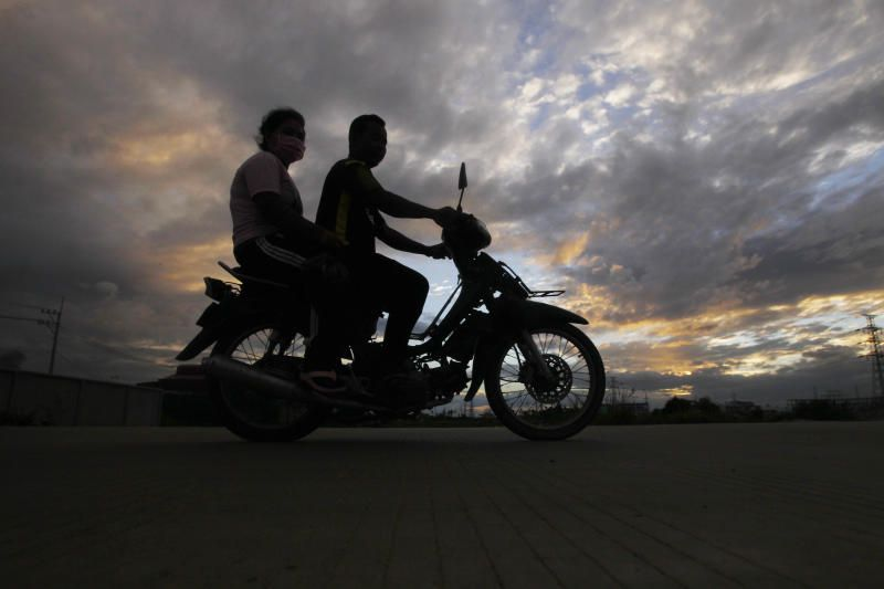 A couple are silhouetted as they ride on a motorcycle back to their home in Chres village on the outskirts of Phnom Penh, Cambodia, early Sunday morning, July 26, 2021. - AP