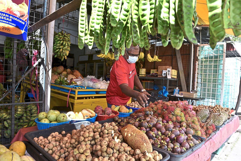 Abdul Rahman arranging his supply of rambutans and mangosteens in Bayan Lepas.
