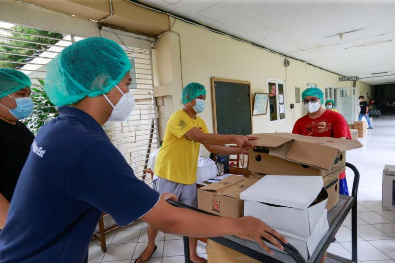 Healthcare workers distribute food at a catholic church training center turned into a self-isolation shelter for coronavirus disease (Covid-19) patients in Jakarta, Indonesia. - Reuters