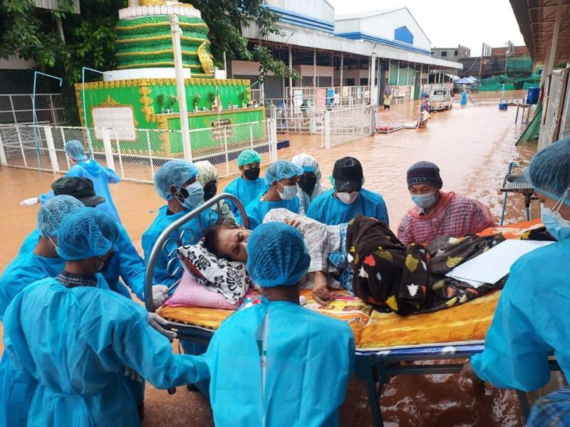 Volunteers in protective suits carry a Covid-19 patient lying on a hospital bed as they try to relocate patients who are dependent on oxygen from the Covid-19 center due to the flood in Myawaddy, Karen state, Myanmar. - Reuters