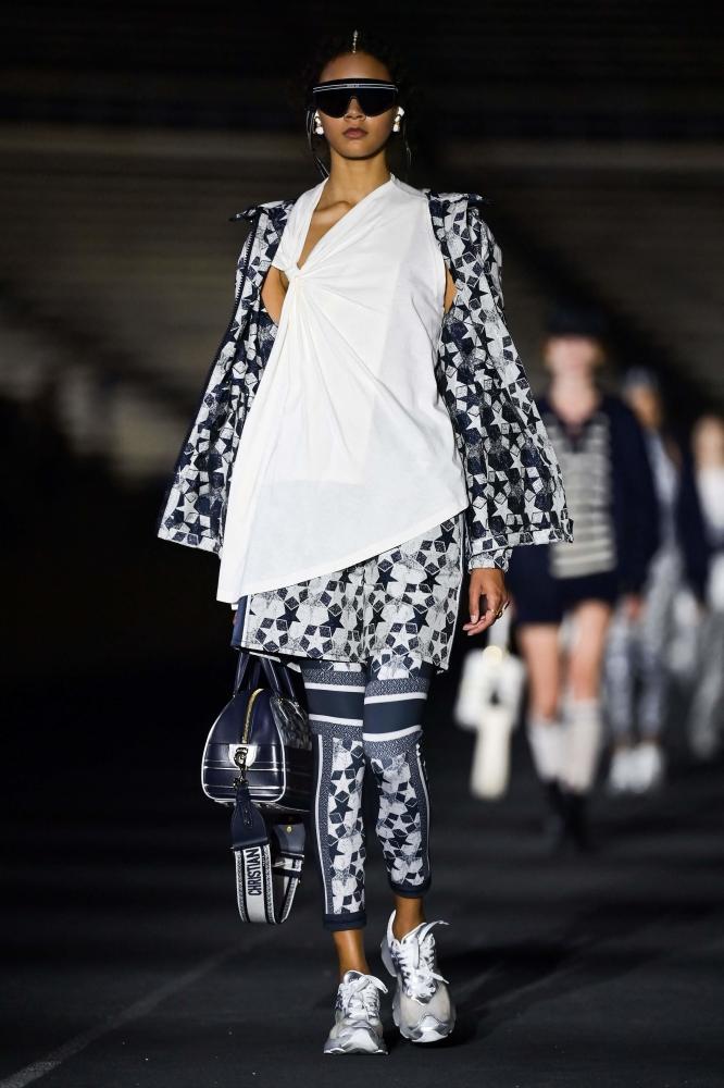 Ένα σπορ ζευγάρι εμπριμέ κολάν Dior με ασορτί μπουφάν.