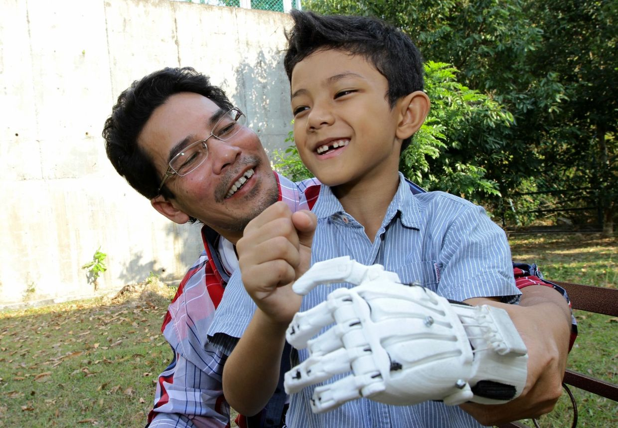 Muhammad Muqri Mifzal (right) smiles as he wears a new mechanical limb which was crafted by Sujana using a 3D printer.