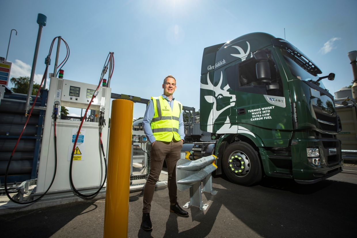 Stuart Watts, a director of Glenfiddich parent company William Grant & Sons, stands by a fuelling station next to their truck, that runs on whiskey-by-product based biogas, in Dufftown, Scotland. – Photo: William Grant & Sons, via Reuters
