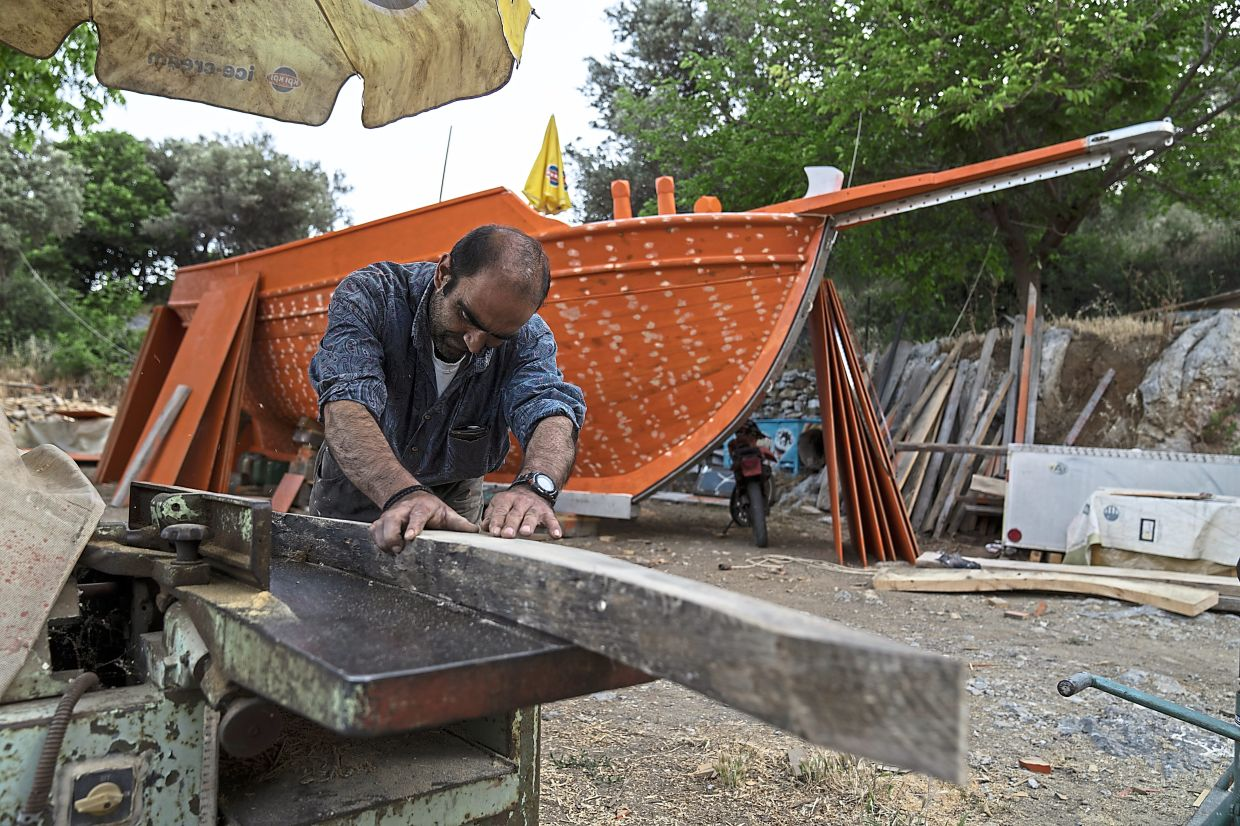 Kiassos, one of the last remaining boatbuilders on Samos island, uses a hand plane to shape wood to be used for the frame of a traditional boat at his mountain boatyard in the village of Drakaioi.