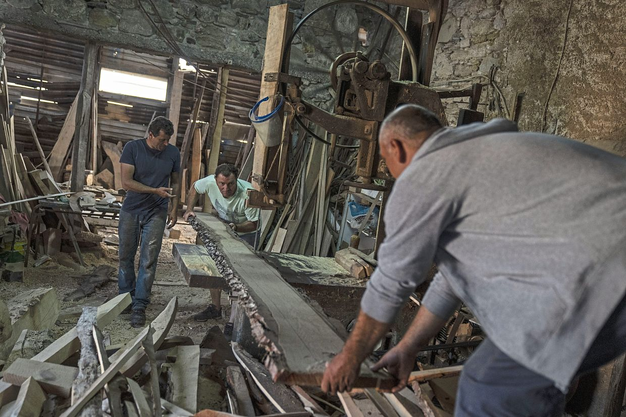 Boatbuilders using a bandsaw to shape wood to be used for the frame of a traditional boat in Karlovasi, Samos Island.