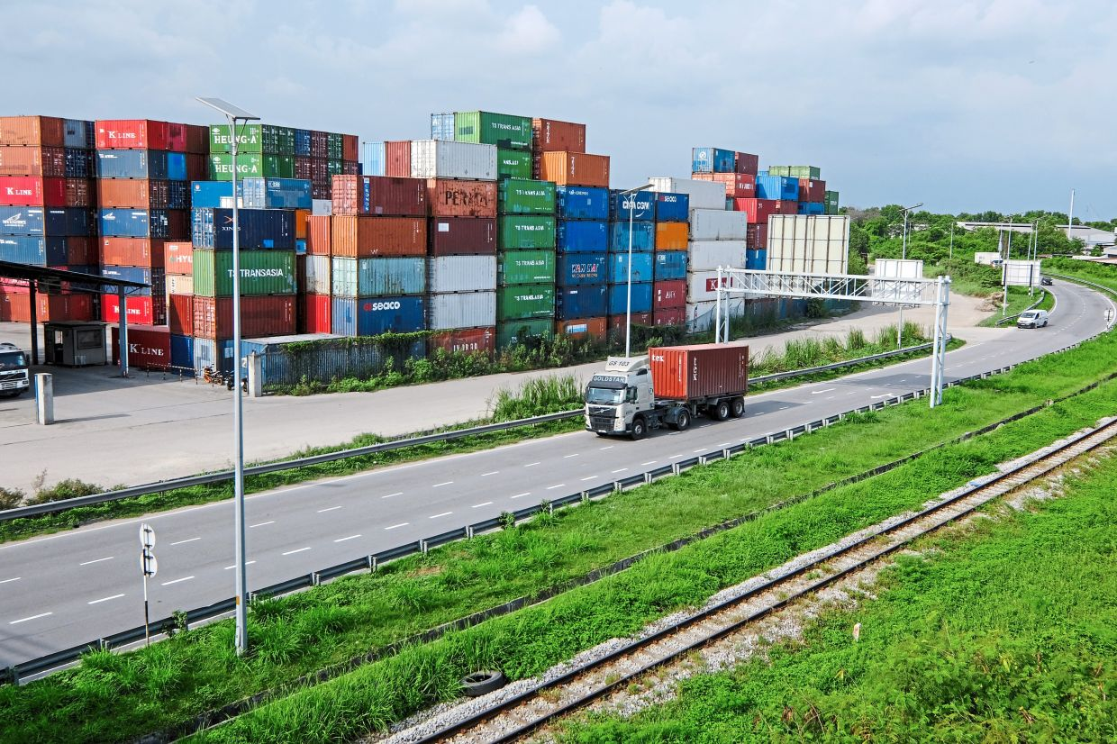 Good sign: A truck is seen travelling past stacked containers at Northport in Port Klang. Rising export numbers are seen as a positive indicator for the economy. ― Bloomberg