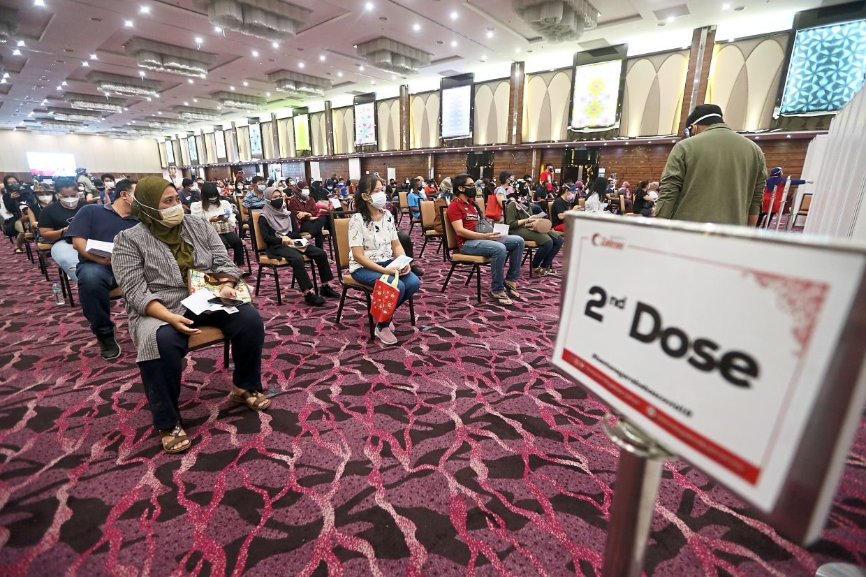 Fast pace: Recipients waiting for their turn at the IDCC Shah Alam vaccine administration centre. As of July 29, official data showed that about 1.96 million people in Selangor and Kuala Lumpur out of a total of 6.1 million adults had received their two doses.