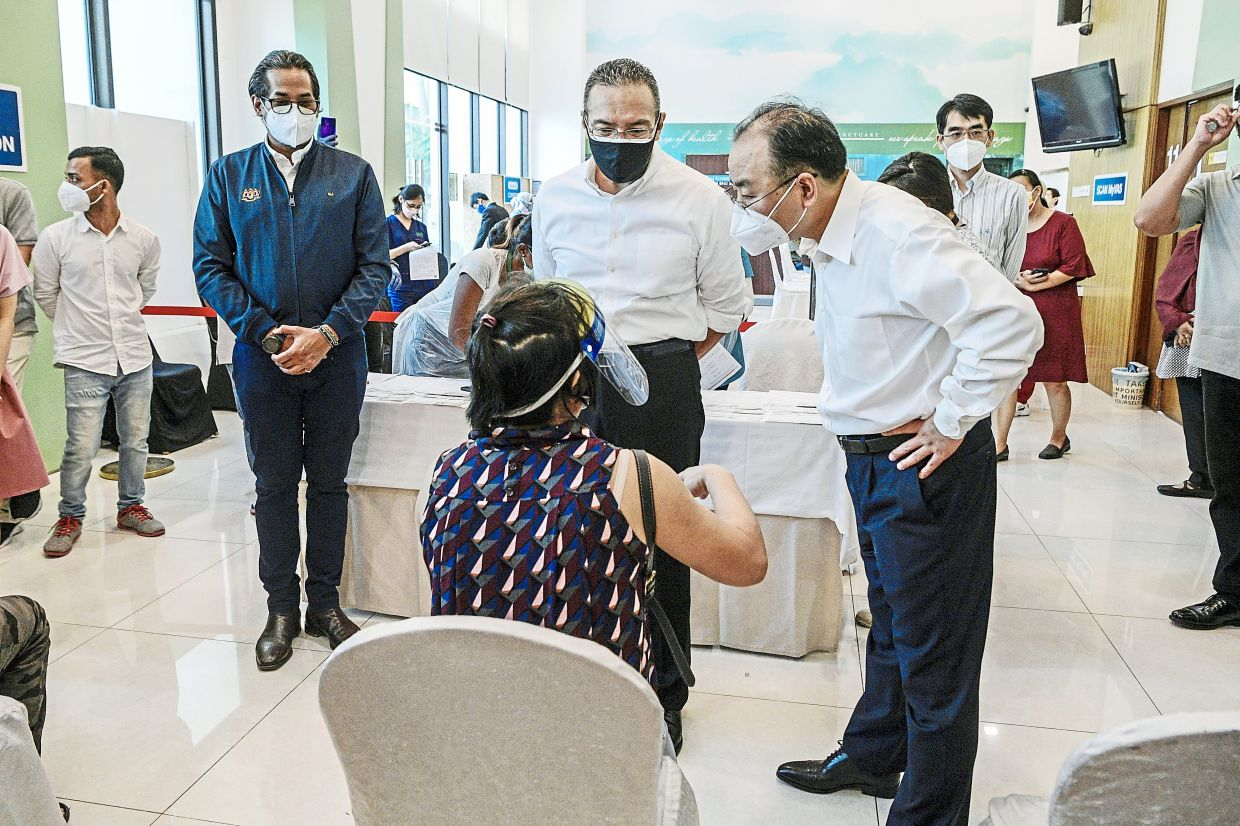 All done: Ouyang (right) talking to one of the Chinese nationals who turned up for the vaccination as Foreign Minister Datuk Seri Hishammuddin Hussein (centre) and Khairy look on. — Bernama