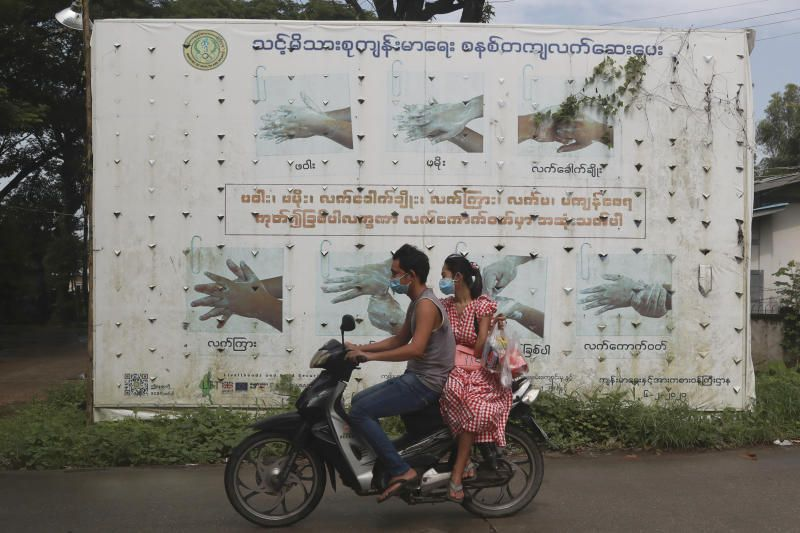 People wearing face masks to help curb the spread of the coronavirus ride a motorcycle past a Health Ministry public information campaign billboard about proper hand washing in Shwe Pyi Thar township in Yangon, Myanmar. - AP