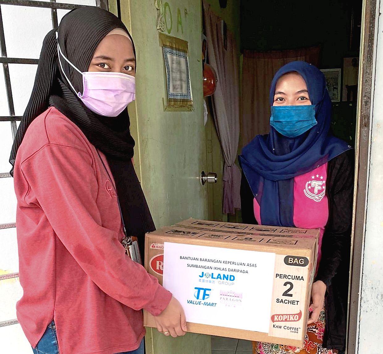 A Paragon Market Place representative (left) distributing a food parcel to a resident at Kampung Melayu Majidee in Johor Baru.