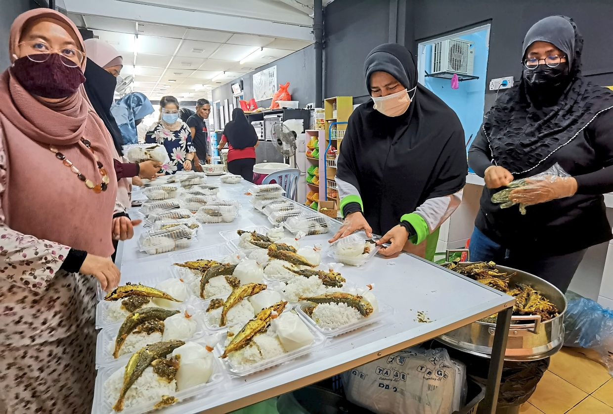 Volunteers preparing food for the homeless who prefer fresh and warm meals. — Filepic