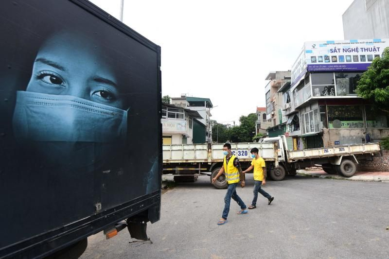 Local residents walk past a make-shift barricade of parked trucks to stop unauthorised travel at a neighbourhood in Hanoi amidst the government imposed two-week lockdown to stop the spread of the Covid-19 coronavirus. - AFP