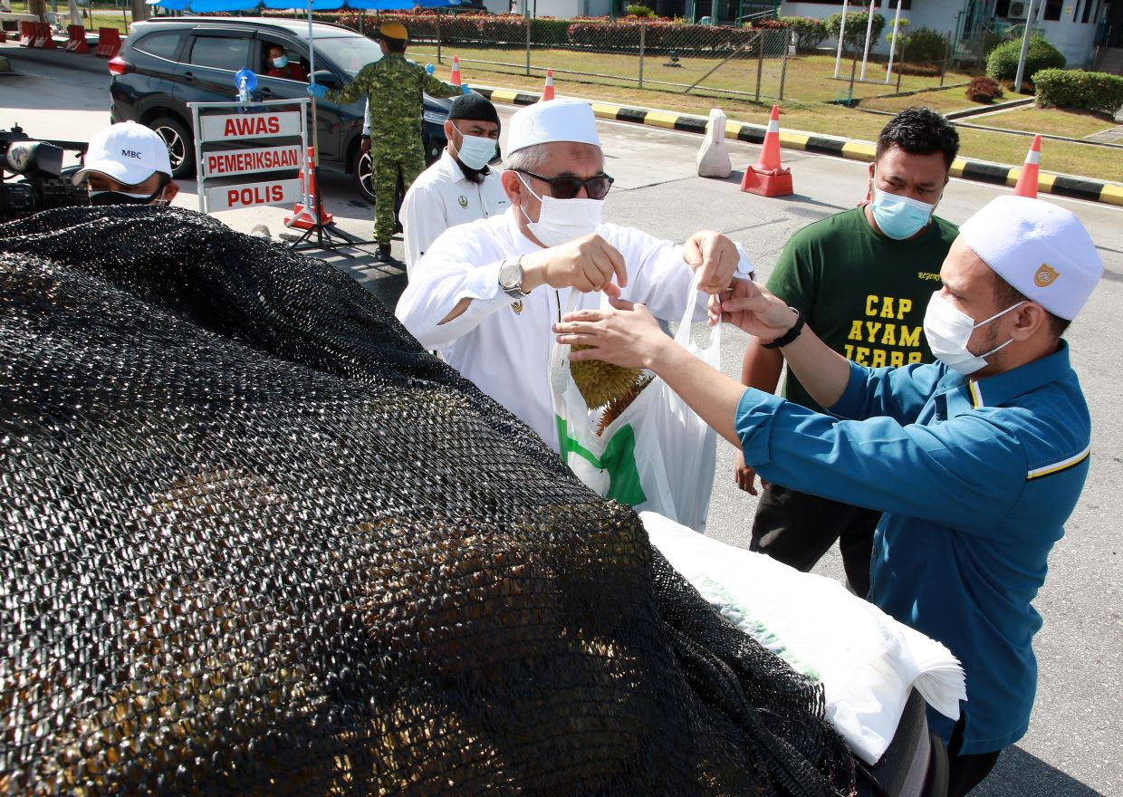 Razman Zakaria (in white kopiah) distributed the durians to the frontliners for their contribution.