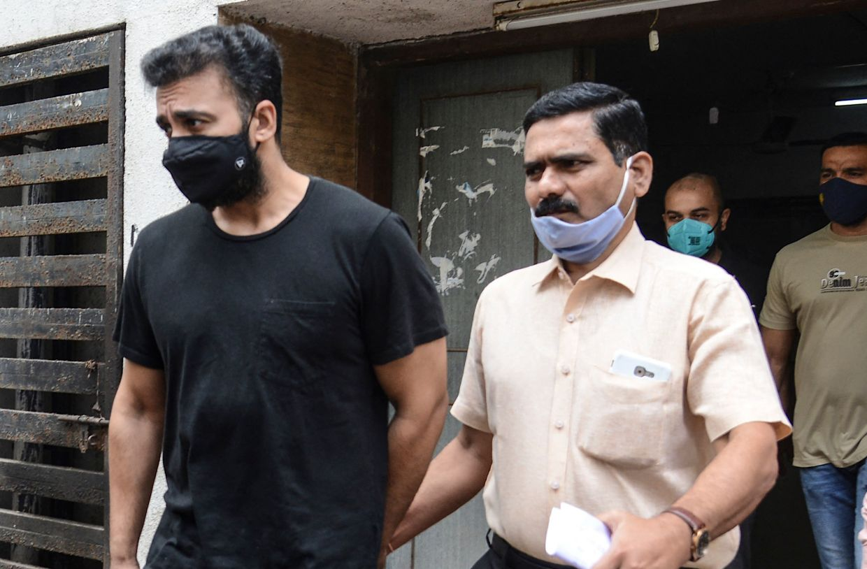 Mumbai Police's Crime Branch team escort Bollywood actress Shilpa Shetty's husband Raj Kundra (left) for allegedly producing and broadcasting pornographic films online, in Mumbai on July 27, 2021. Photo: AFP