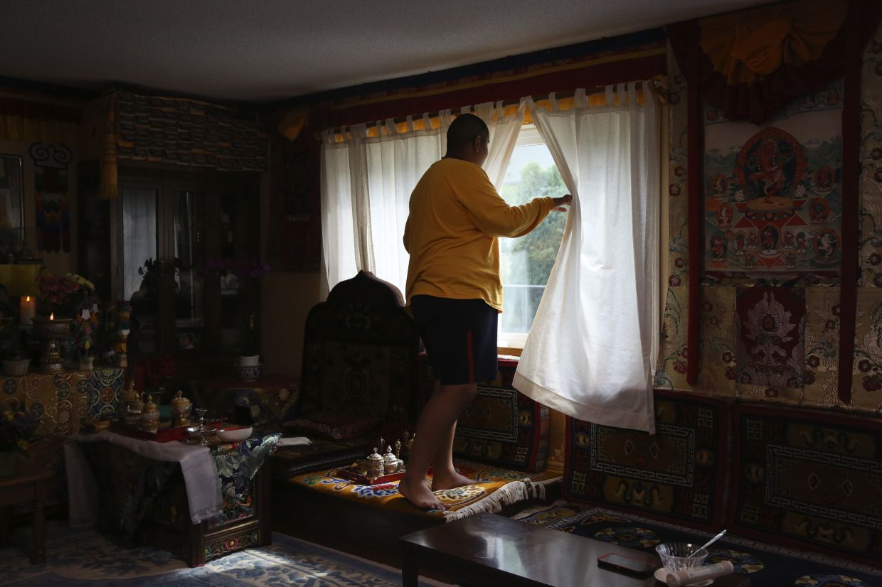Jalue Dorje, 14, looks out the window for his father as they clean up after a weekend of ceremonies paying homage to Guru Rinpoche, the Indian Buddhist master who brought Tantric Buddhism to Tibet.