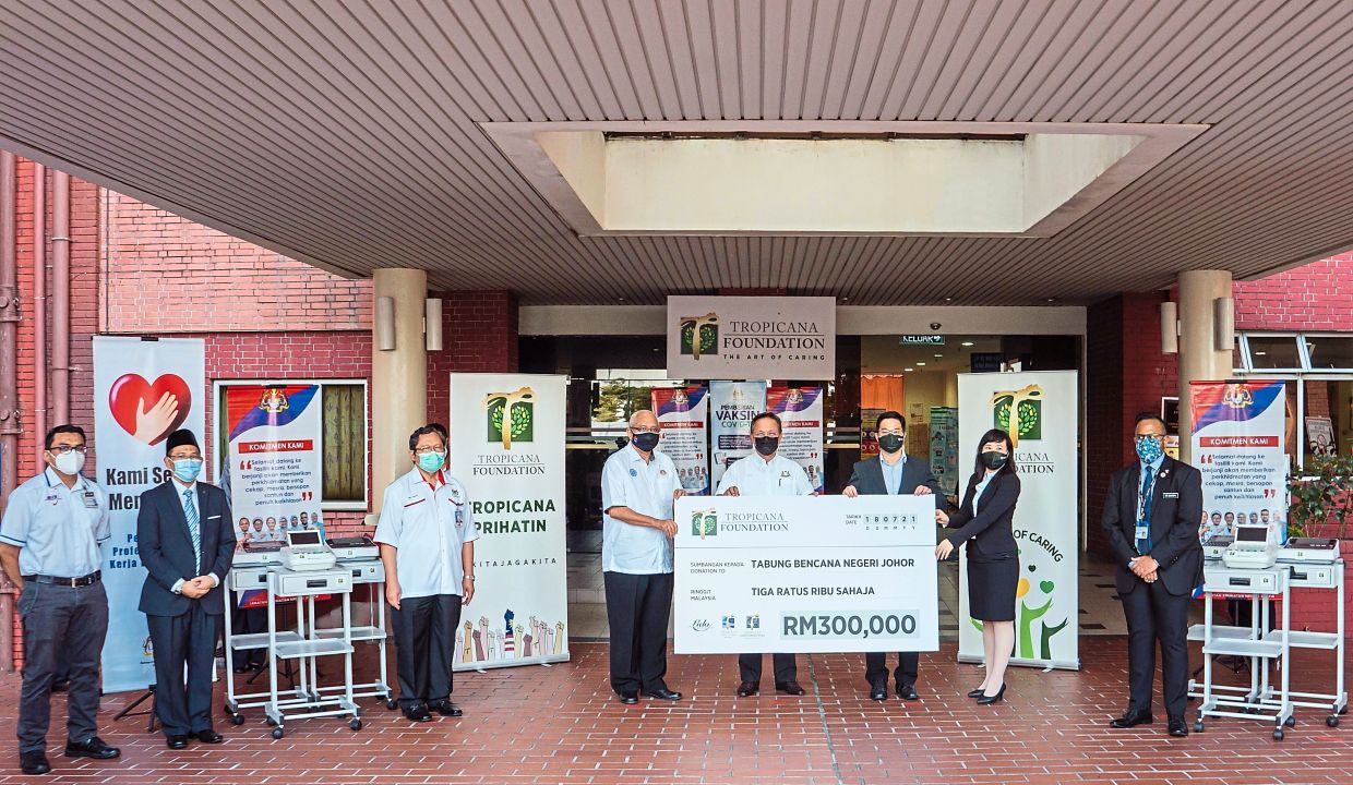 At Tropicana's mock cheque presentation of RM300,000 to Johor Disaster Relief Fund (from left) are Dr Mohd, Dr Mohtar, Mohd Noh, Dr Aman, Hasni, Han Ming, Karen and Dr Sharath.