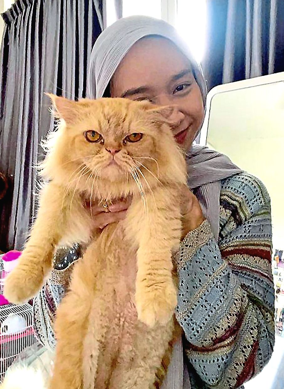 Saidatul Aina holding up her feline friend Boba that has kept her company through some challenging days lately.