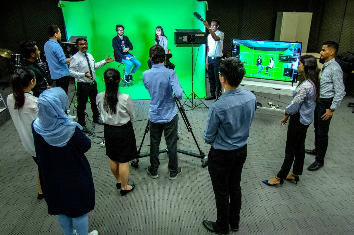 Edwin (third from left, in a necktie) demonstrating chroma keying – a visual-effects and post-production technique – at APU green screen production floor.