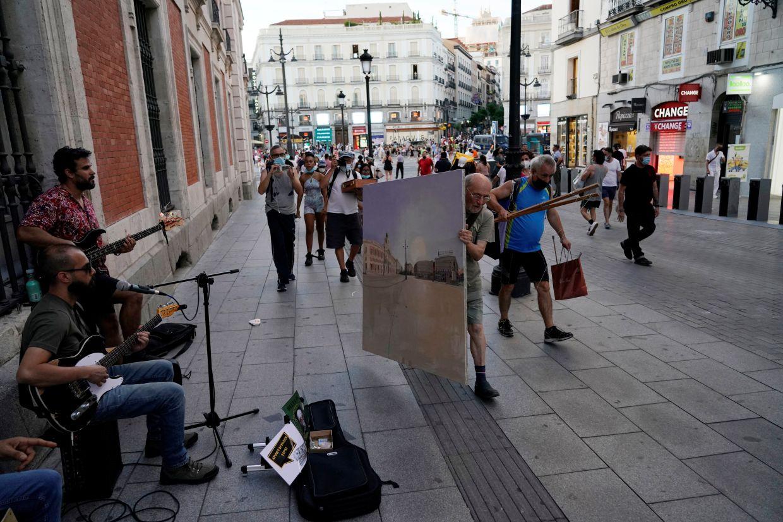 López lleva un lienzo pintado con el famoso Puerto del Sol tras una sesión en Madrid.  Foto: Reuters