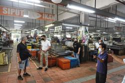 Traders clean up and sanitise stalls for reopening of Batu Lanchang Market