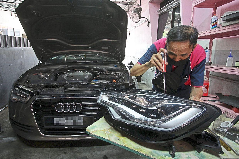 A worker repairing a headlamp at Pink Garage Tyre & Auto Repairs in Kelawai Road, Penang.