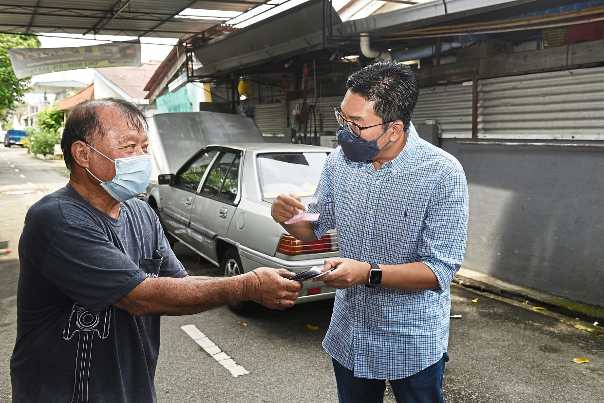 Sim (right) presenting the RM1,000 cash prize to Kook.