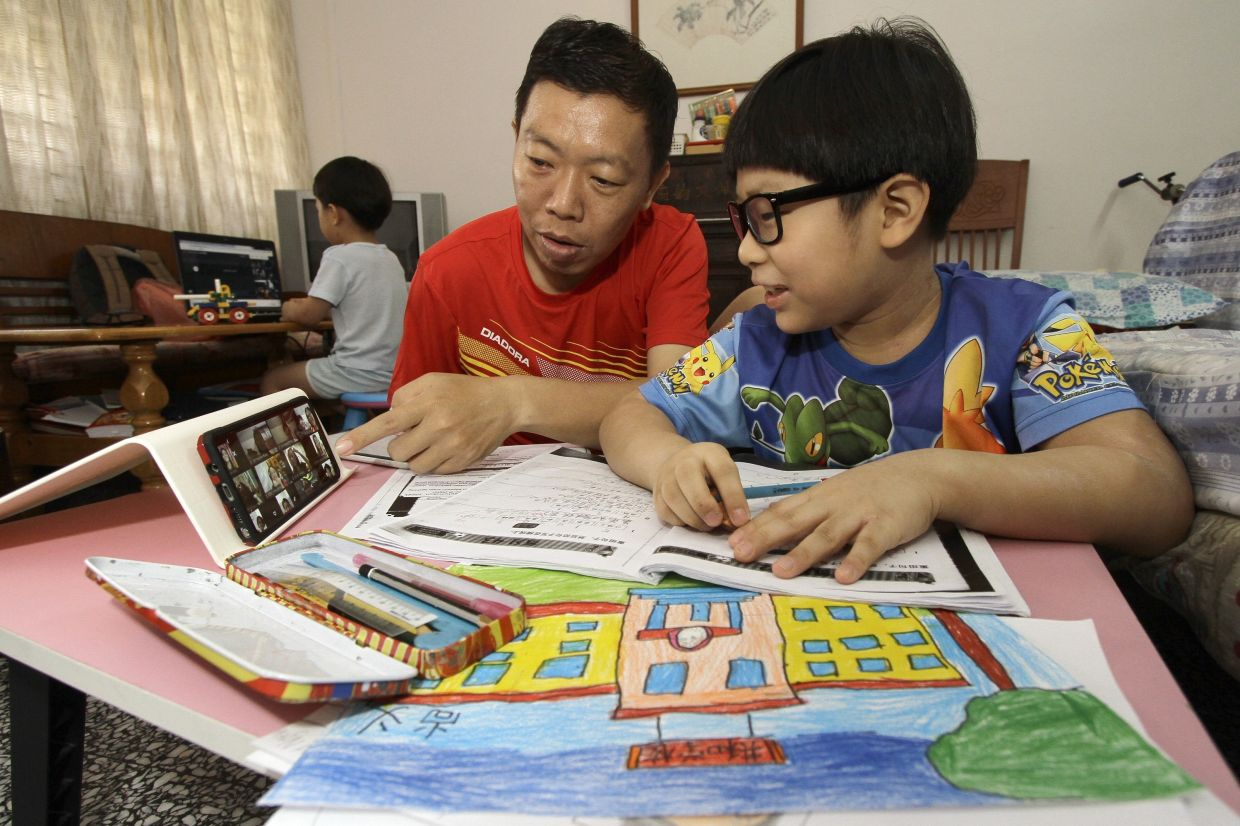 Parents play a vital role in ensuring that their children are up to date with their studies amid the pandemic. — CHAN BOON KAI/The Star