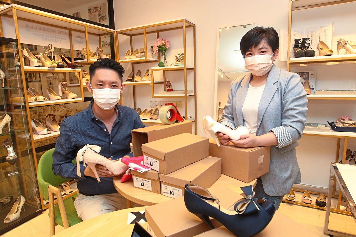 Looi (right) and Gan are selling clothes and shoes online to keep their business afloat. — ART CHEN/The Star
