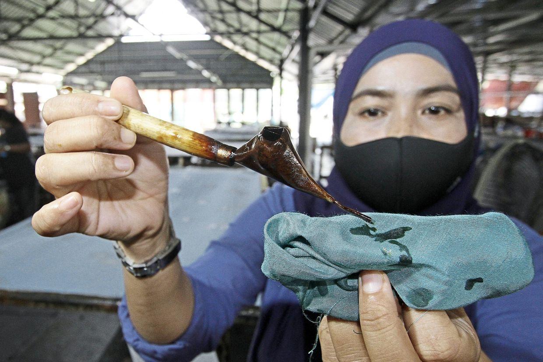Marina Ab Hadi, 45, showing the canting tool used for batik wax design.