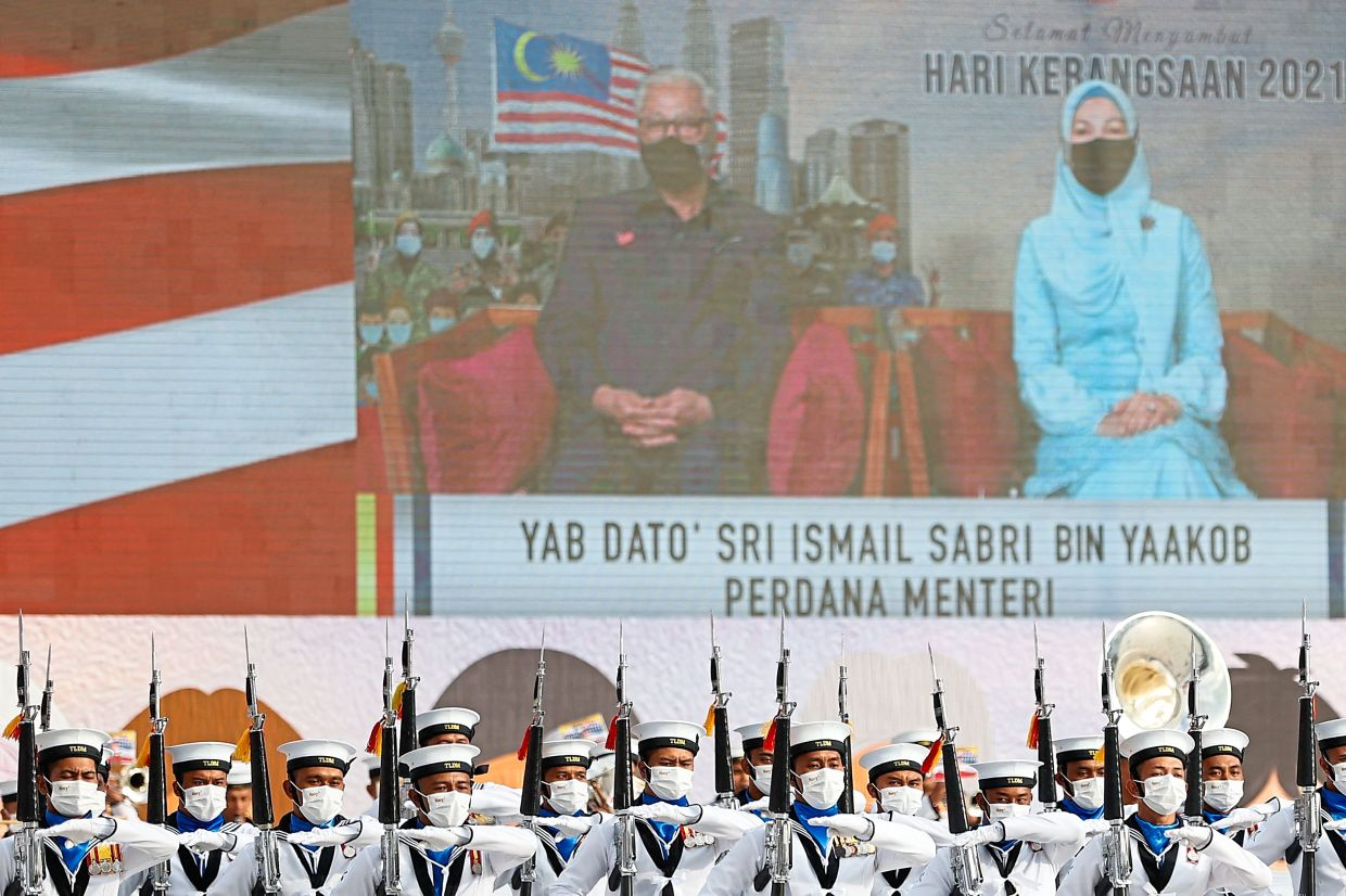 There in spirit: Ismail and his wife Muhaini watching the live telecast as members of the Royal Malaysian Navy take part in the 64th National Day celebrations at National Heroes Square in Putrajaya. — AFP