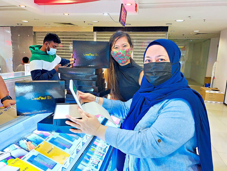 Hayati (right) with Malaysia Women Marathon founder Karen Loh purchasing tablets for the Projek Peranti Pendidikan.