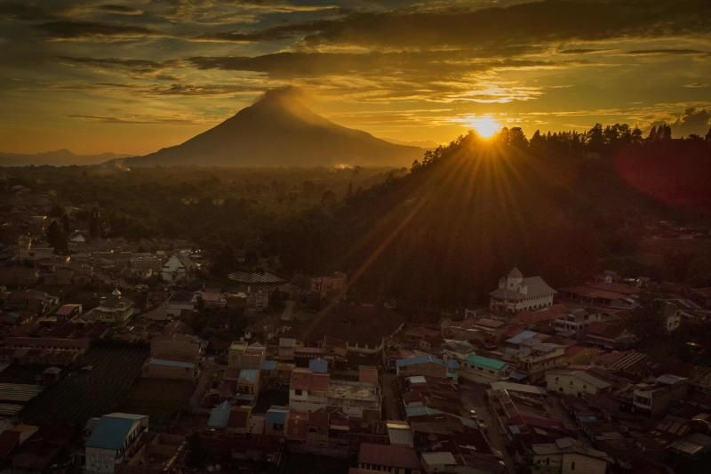 The picture shows shows the sun setting behind Mount Sinabung volcano  in Berastagi, North Sumatra in Indonesia. The 2,460m-high volcano erupted in 2010 after a hiatus of 400 years and has been continuously erupting since September 2013. - AFP