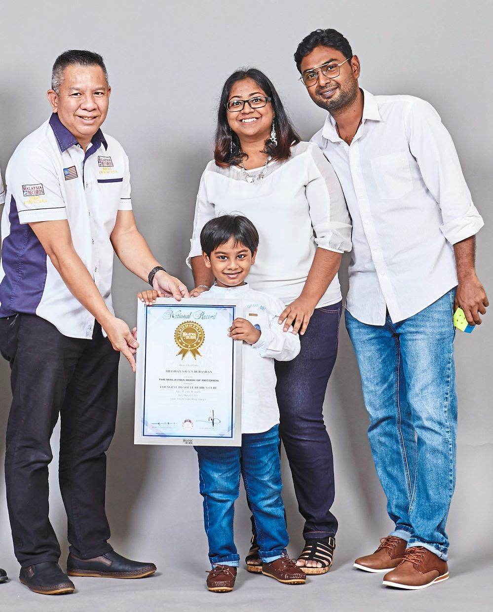 Young Thashan receiving his certificate from Malaysia Book of Records' senior record consultant Edwin Yeoh Tiong Chin (left) as his parents look on.