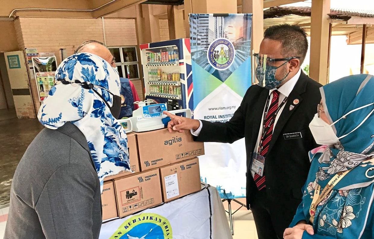 Dr Sharath (second from right) inspecting the syringe pumps donated by RISM while Dr Fara Diva (left) looks on.