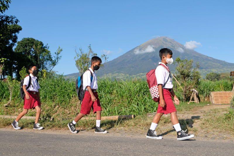 Siswa sekolah dasar yang mengenakan masker berjalan di lereng Gunung Sinduru, desa Midari untuk menghadiri kelas, ketika sekolah dibuka kembali secara uji coba setelah pemerintah memperluas pembatasan untuk mengekang penyebaran Covid-19 di Temanjung, Provinsi Jawa Tengah, Indonesia 7 September , 2021 Dalam foto ini, diambil oleh Antara Foto via Reuters