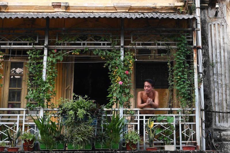 Seorang pria melihat dari balkonnya di Hanoi, selama penguncian yang diberlakukan pemerintah untuk membendung penyebaran virus corona Covid-19.  Menghadap jalan-jalan yang sepi, balkon kecil Hanoi telah menjadi tempat perlindungan karena penduduk kota yang tertutup meremas meja, tikar yoga, dan bangku yang nyaman untuk minum kopi di udara segar.  - Agen Pers Prancis