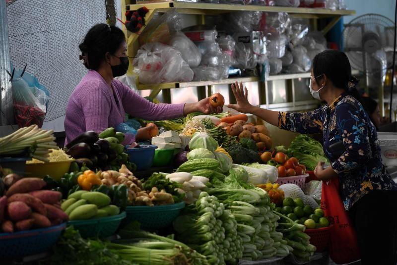 Seorang wanita membeli bawang di pasar di Phnom Penh.  - Agen Pers Prancis