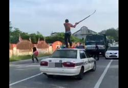 Scythe-swinging shirtless man goes amok on top of police car in Gopeng