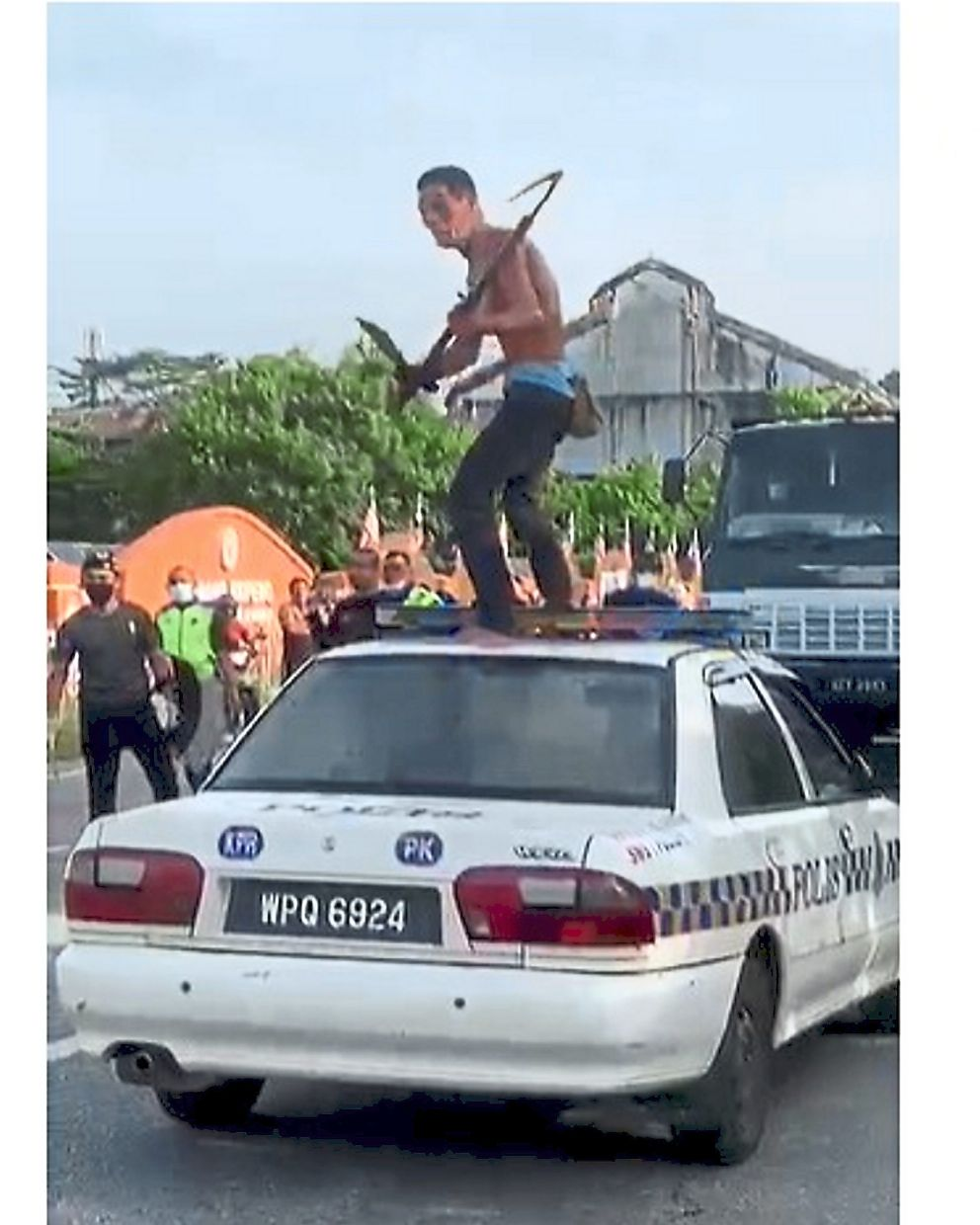 Tense moment: A screencap of a video showing the shirtless man seen standing on top of a police mobile vehicle with the machete and scythe in hand while screaming at policemen who had him surrounded.