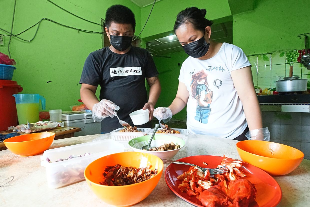 Jimmy and Shiren packing kolo mee orders at their flat in Taman Tampoi Utama. — Photos: THOMAS YONG/The Star